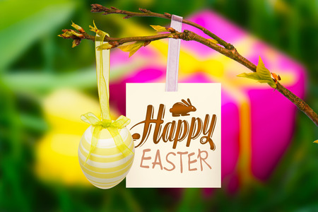 happy easter graphic against pink gift box and yellow tulips photo