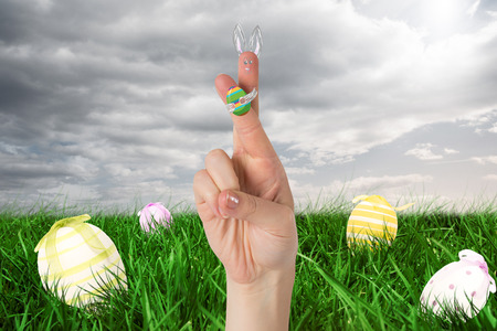 green hand: Fingers as easter bunny against green hand painted easter egg