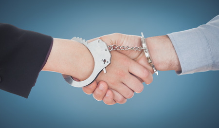 restraining device: Business people in handcuffs shaking hands against blue