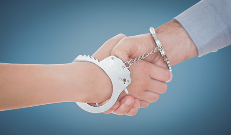 handcuffed hands: Handcuffed business people shaking hands against blue
