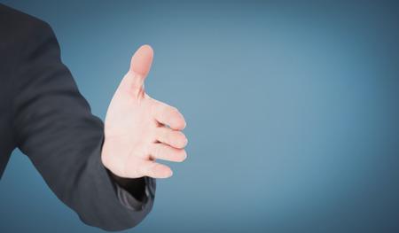 extending: Businessman extending arm for handshake against blue
