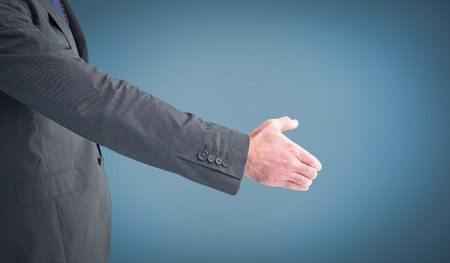 hand out: Businessman holding his hand out against blue