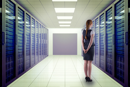 hands behind back: Redhead businesswoman with hands behind back against server room with towers Stock Photo