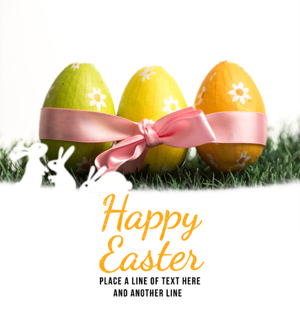 easter sunday: happy easter against three easter eggs wrapped in pink ribbon Stock Photo