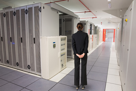 hands behind back: Businesswoman standing with hands behind back against data center
