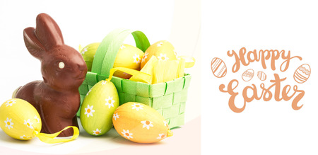 Happy Easter greeting against easter eggs in a basket with chocolate bunny