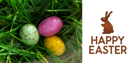 nestled: happy easter graphic against small easter eggs nestled in the grass Stock Photo