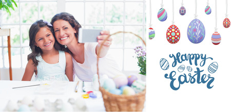 curly hair child: Happy mother and daughter taking selfie against happy easter graphic Stock Photo