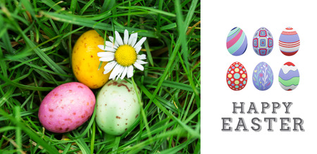 nestled: happy easter graphic against small easter eggs nestled in the grass with a daisy Stock Photo