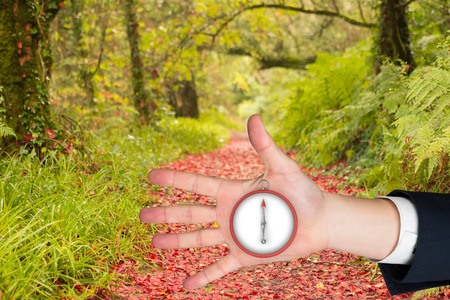 Hand with fingers spread out against peaceful autumn scene in forest photo