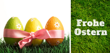 frohe: Frohe ostern against grass background Stock Photo