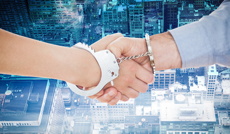 handcuffed hands: Handcuffed business people shaking hands against new york Stock Photo