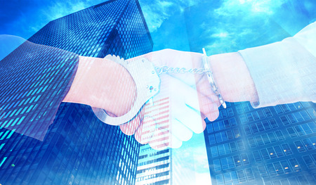 restraining device: Business people in handcuffs shaking hands against low angle view of skyscrapers