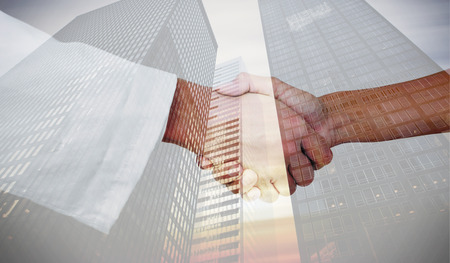 extreme angle: Extreme closeup of a doctor and patient shaking hands against low angle view of skyscrapers Stock Photo