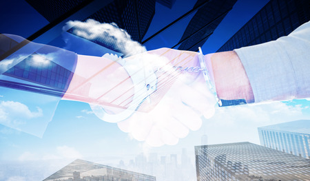 restraining device: Business people in handcuffs shaking hands against skyscraper Stock Photo