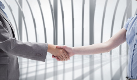 Handshake between two women against white room with large window overlooking city photo