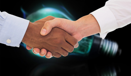 glowing light bulb: Close-up shot of a handshake in office against glowing light bulb Stock Photo