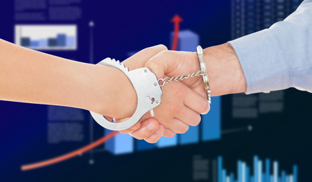 restraining device: Handcuffed business people shaking hands against business interface with graphs and data