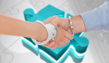 Handcuffed business people shaking hands against jigsaw