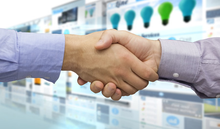technology agreement: Hand shake in front of wires against screen collage showing business advertisement
