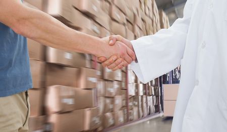 medical distribution: Mid section of a doctor and patient shaking hands against forklift machine in warehouse Stock Photo