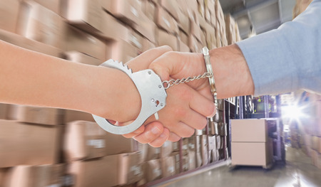 Handcuffed business people shaking hands against forklift machine in warehouse