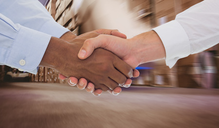 stacker: Close-up shot of a handshake in office against worker with fork pallet truck stacker in warehouse