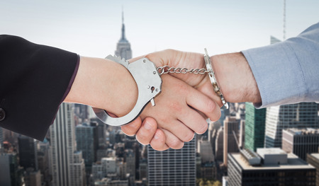 restraining device: Business people in handcuffs shaking hands against new york