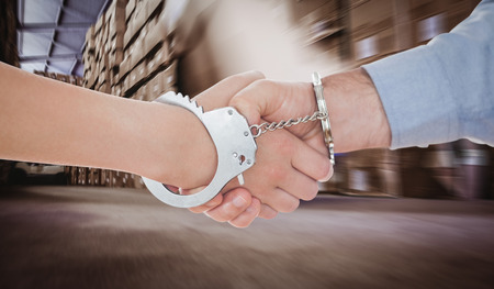 handcuffed hands: Handcuffed business people shaking hands against worker with fork pallet truck stacker in warehouse Stock Photo