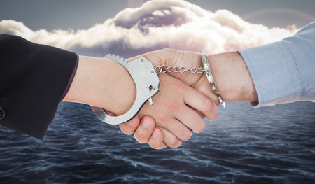 restraining device: Business people in handcuffs shaking hands against calm sea with lighthouse Stock Photo