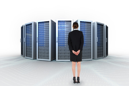 hands behind back: Young businesswoman standing with hands behind back against server towers
