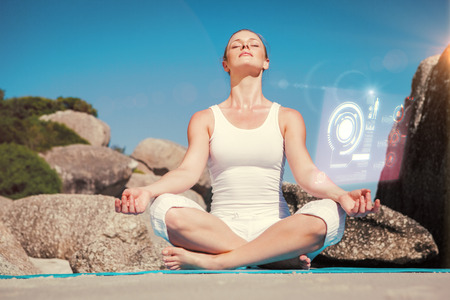 beach mat: Blonde woman sitting in lotus pose on beach on mat against fitness interface Stock Photo