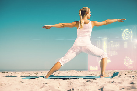 warrior pose: Calm woman standing in warrior pose on beach against fitness interface