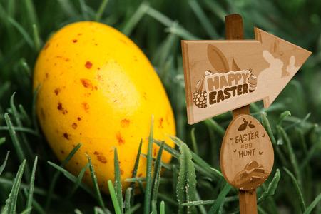speckled: Easter egg hunt sign against yellow speckled easter egg Stock Photo