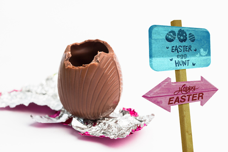 unwrapped: Easter egg hunt sign against easter egg unwrapped in pink foil with bite taken out Stock Photo