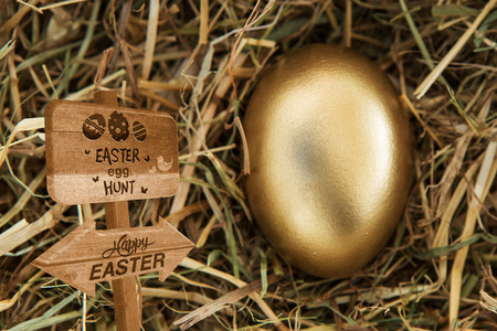 gold eggs: Easter egg hunt sign against golden egg in the straw