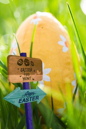 nestled: Easter egg hunt sign against easter egg wrapped in foil nestled in the grass
