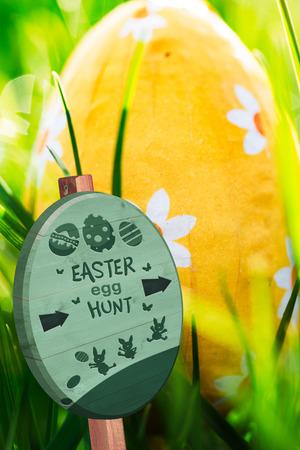 nestled: Easter egg hunt sign against easter egg nestled in the green grass Stock Photo