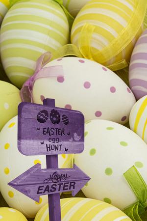 nestled: Easter egg hunt sign against easter eggs nestled together