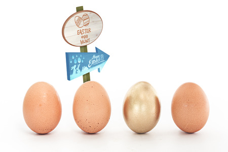 'odd one out': Easter egg hunt sign against four eggs in a row with one gold one Stock Photo