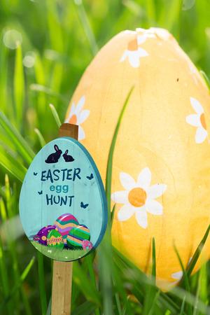 nestled: Easter egg hunt sign against orange easter egg nestled in the grass