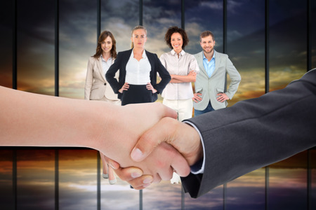 Close up of a handshake against room with large window looking on landscape photo