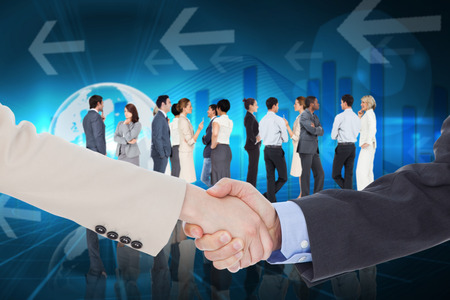Smiling business people shaking hands while looking at the camera against global business graphic in blue photo