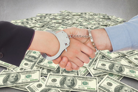 restraining device: Business people in handcuffs shaking hands against pile of dollars