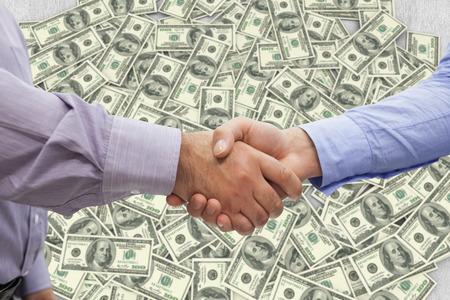 men shaking hands: Men shaking hands against pile of dollars