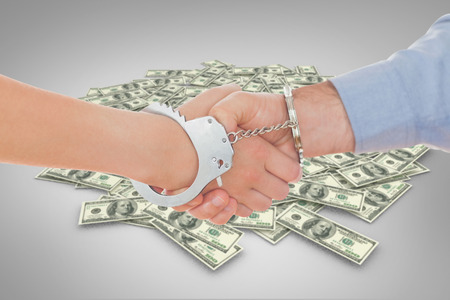 handcuffed hands: Handcuffed business people shaking hands against pile of dollars Stock Photo