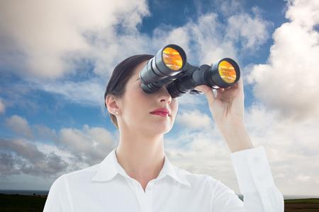 mujer mirando el horizonte: Mujer de negocios mirando a trav�s de binoculares contra el cielo azul con nubes blancas