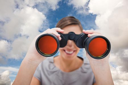 conclusion: Mujer que mira con catalejos contra el cielo azul con nubes blancas Foto de archivo