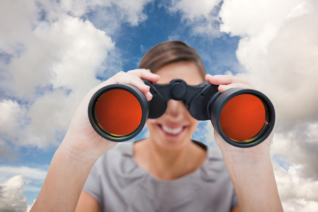 finding: Woman looking through spyglasses against blue sky with white clouds Stock Photo