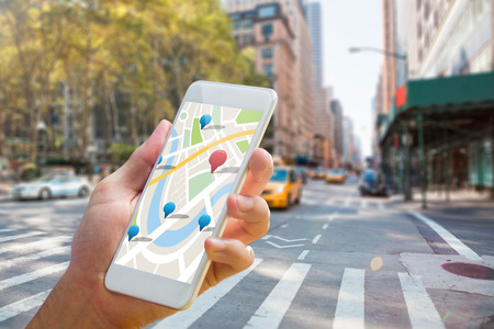 city living: Man using map app on phone against new york street